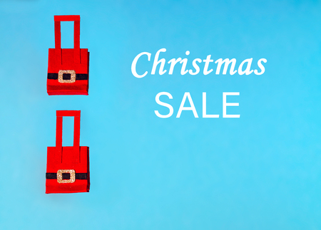 Red Christmas shopping bag on blue background. Santa Claus shopping bags on blue. Copy space. Christmas theme.  Paper craft Christmas theme. Christmas sales concept.  Colourful pastel Christmas bags.  Shopping concept. Stockfoto