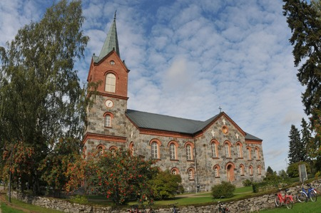 made in finland: Old church made of big grey bricks surrounded by rowan trees in Juva, Finland