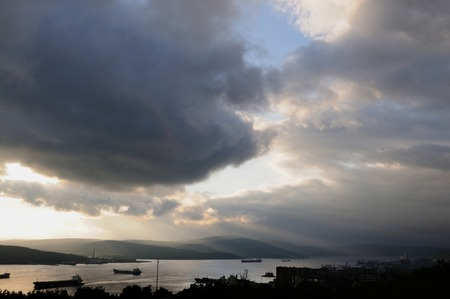 penetrated: Heavy sky penetrated by the sun beams hanging over the ships passing Kola Bay, Murmansk, Russia