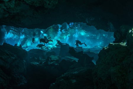 A group of divers is swimming in the waters of underwater cavern, Kukulkan cave, Yucatan peninsula, Mexico