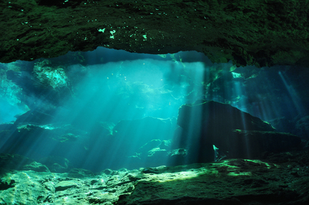 penetrate: Sunbeams penetrate through the waters of Chac mool cave producing mysterious reflections on the surface in the background, Yucatan peninsula, Mexico