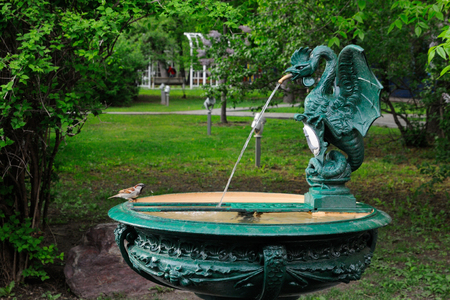 A sparrow is drinking water from a fountain in a form of basilisk, Bauman Garden, Moscow, Russia