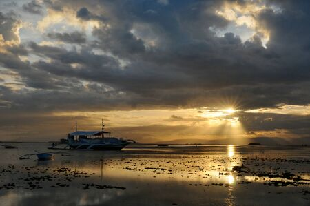The sun is broking through the heavy clouds during the sunset with small boats anchored in a harbor, Panglao, Philippines Reklamní fotografie