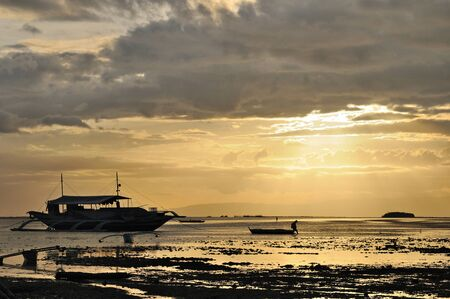 Tired fisherman is pulling his boat on the sunset, the other boats are already anchored, Panglao, Philippines