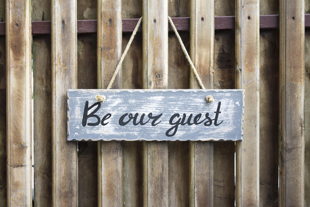 Wooden table with lettering Be our guest Stock Photo