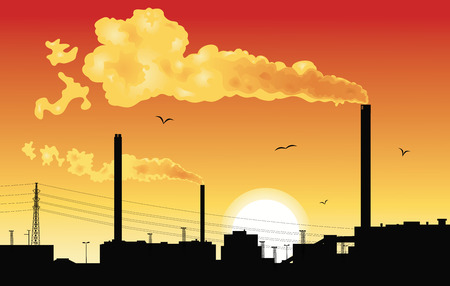 Silhouette of a factory with smoke coming out of chimneys at sunset.