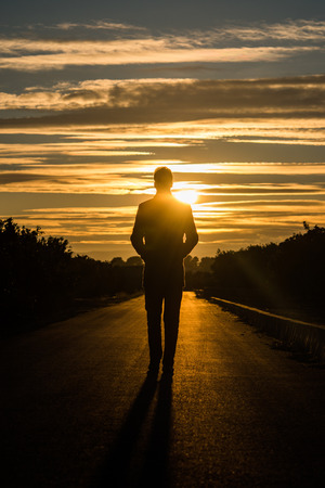 Silhouette of a man walking on a road at sunset. Фото со стока