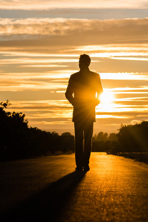 Silhouette of a man walking on a road at sunset. Banco de Imagens - 81497845