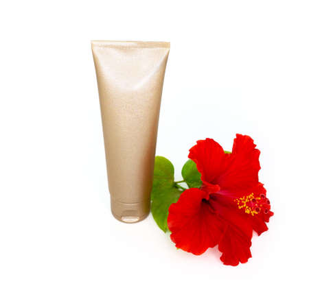 Golden cream bottle and tropical flower on the white background. Stock Photo