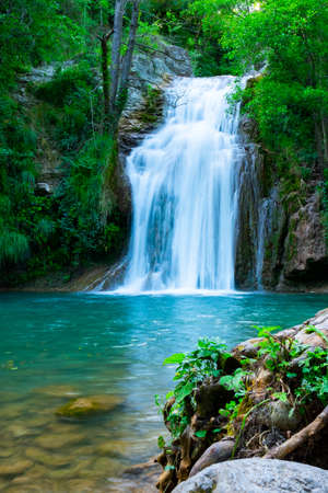 A large beautiful waterfall in a forest with blue water and a trees. Standard-Bild