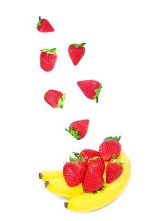 Falling strawberry and bananas on white background photo