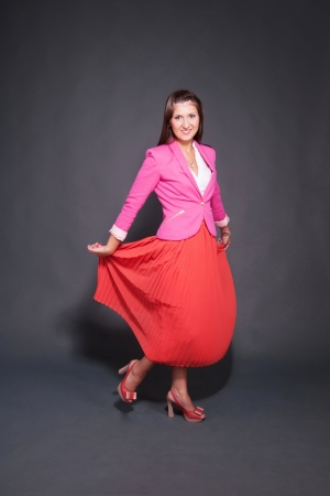Hot young brunette in red skirt and pink jacket against grey background photo