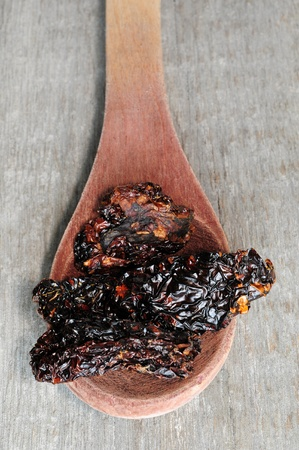 Traditional Italian style sun dried black tomatoes in spoon
