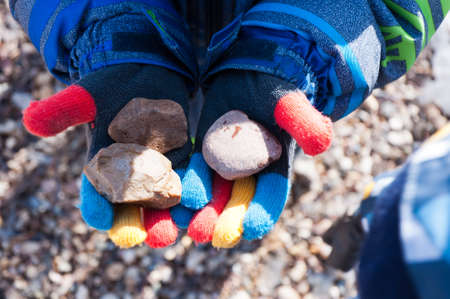 A boy in multi-colored gloves holds three stones.