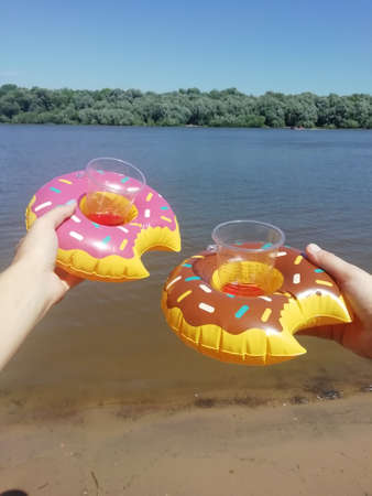Round inflatable circles in the form of a donut in the hands of two girls. A cup is inserted into the inflatable ring.