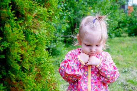 A girl gardener stands near the Christmas trees in a pink jacke. Stok Fotoğraf