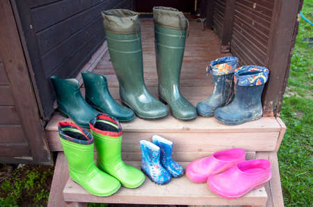 Old dirty rubber boots of a big family stand on the wooden floor of a country house porch lit by summer sun with green grass. Short rubber country goloshes.