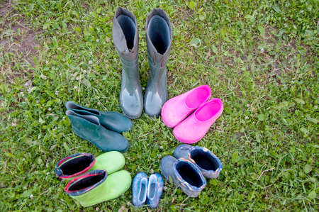 Six pairs of old rubber boots of a big family stand on the grass. Short rubber country goloshes.