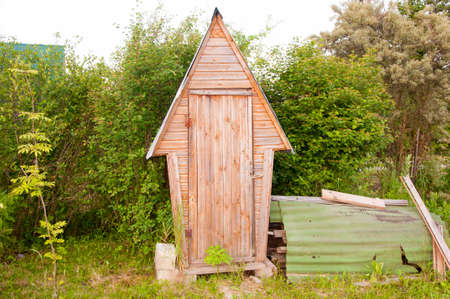 toilet in the garden WC cabin toilet in the form of a wooden cottage house near a countryside road. Stok Fotoğraf