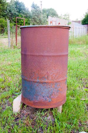 Old metal rusty barrel oil in the garden.
