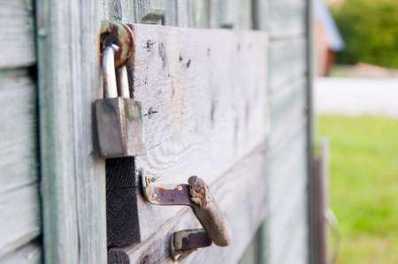 The old lock was used to lock old wooden doors. The steel silver lock reliably locks old doors, doors with peeling paint.
