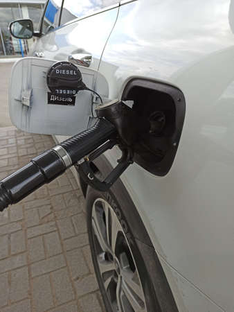 Refueling the gas tank with a gun. Refueling a white car at a gas station. Black gun
