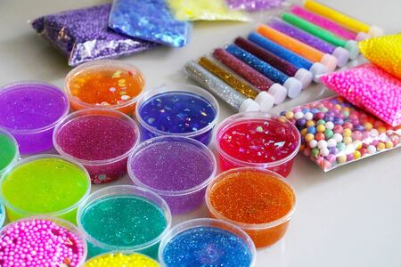 Defocused colorful slimes inside plastic boxes. Set of kids gunk toy, close up view. How to make fluffy slime at home. Coloful photo