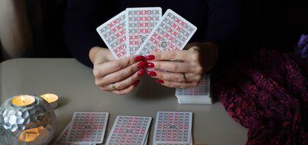 Tarot reader picking tarot cards, near burning candles.