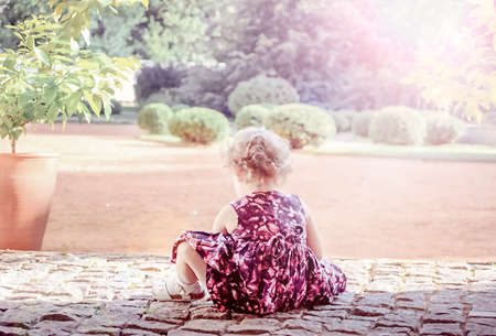 Blurred view of a little curly girl who sits on a stone walkway in a summer park. High quality photo