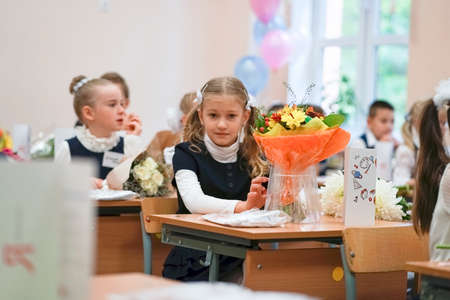 Defocused View of Little first-graders, go to school on knowledge day - September First. Student of elementary school in uniform with bows posing in classroom. High quality photo