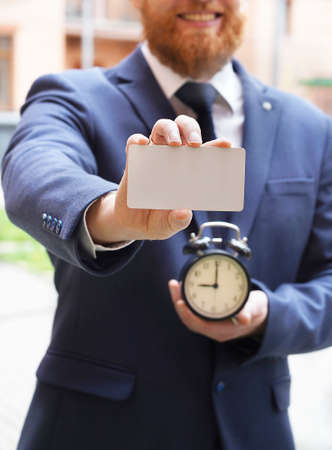 Blurred man sholds a blank card in one hand and an alarm clock