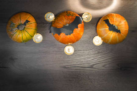Blurred autumn composition for the holiday helloween, three pumpkins, bats and candles. High quality photo