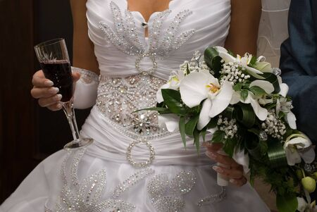 lustre: Bride hold bouquet and glass of wine Stock Photo