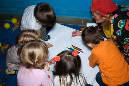 denote: Five children and clown draw on white paper in nursery at the same time