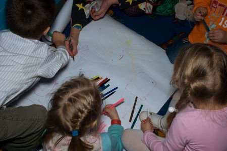 denote: Four children and clown draw on white paper in nursery at the same time