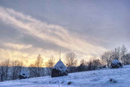 Rural winter mountain landscape with sundown and hayricks under the snow. HDR image photo