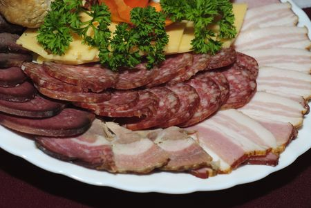 collation: Plate with collation close up on table. Peaces of various sausage and flower from carrot