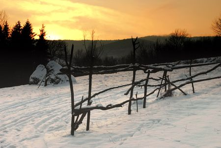 Rural winter mountain landscape with sundown and hayricks under the snow, and wooden fence. photo