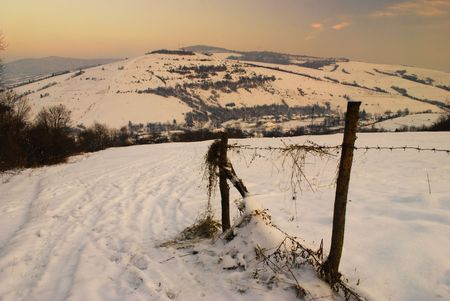 Rural winter mountain landscape with fence and road under the snow. Stock Photo