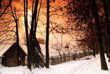 Rural winter mountain landscape with sundown and road, trees, fence photo