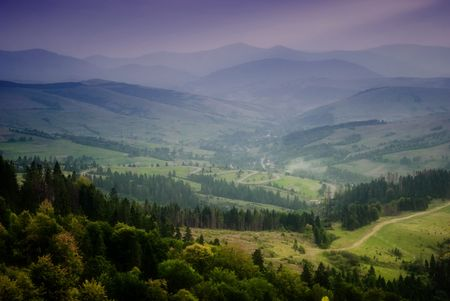 Beautiful sky and forest high up in Carpathian mountains. With view on village after rain with sunrays.