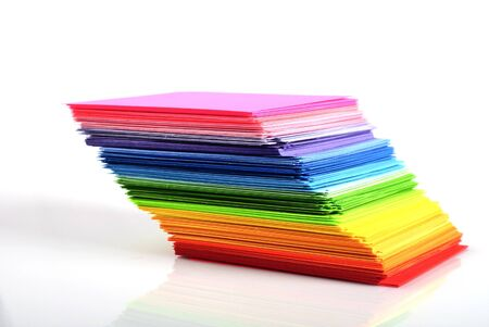 various color paper stack like a rainbow isolated on white photo