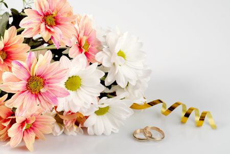 ikebana: Pink  and white daisy with gold ribbon and wedding rings. Still life isolated on white