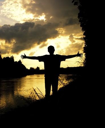 silhouette man arms raised sunset sky landscape photo