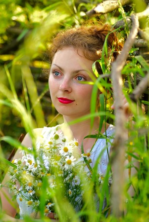 Girl with camomile bunch stand neat the wooden fence. Rural portrait. photo