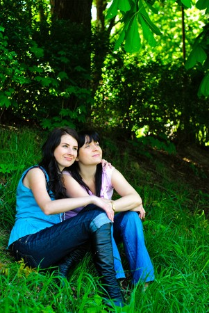 Two sisters sitting on the grass and dreaming and staring into the distance . Outdoor, under the tree. Stock Photo - 7233249