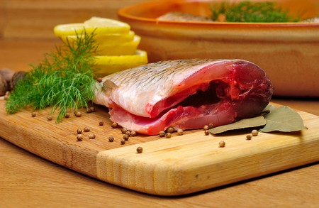 Fish carcass with spices on wooden hardboard, prepared for cooking photo