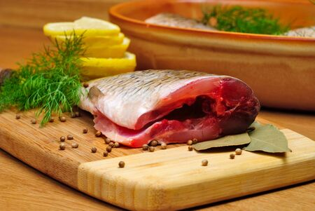 carcass: Fish carcass with spices on wooden hardboard, prepared for cooking