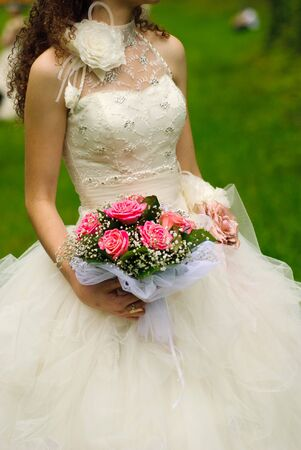 Bride from behind throw the bouquet from pink roses on old wall background photo