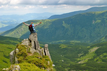 splayed: Woman in montains  on rock with back pack with his arms splayed and say: I love this world